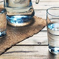 Houte tafel met daarop drie glazen gevuld met water