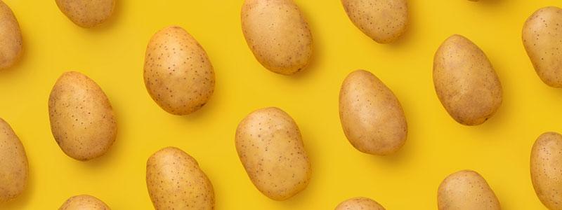 Gele achtergrond met daarop neergelelgd meerdere aardappelen
