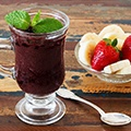 Een tafel met daarop een glas met daarin in acai bessen mouse, een lepel en een schaaltje met wat aardbeien en bananen