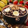 Schaaltje met acai yoghurt, een lepel, een aantal bananen en aardbeien