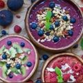 Een tafel met 3 schaaltjes acai bessen yoghurt versiert met wat bessen, frambozen en granen