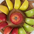 Een houte plank met daarop een cirkel van appel schijfjes met in het midden een hele appel