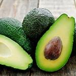 Meerdere avocados bij elkaar waarvan er een door de helft is gesneden en dus de pit te zien is