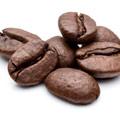 Een klein hoopje bruine koffiebonen, vol met cafeine