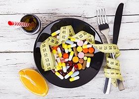 Bord met daarop capsules en een meetlint, bestek, een potje capsules met een rietje erin en een halve citroen