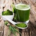 Tafel met chlorella poeder, sprieten en een glas met groene smoothie
