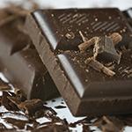 Twee afgebroken stukken pure chocolade met daarnaast wat kleine stukjes chocola