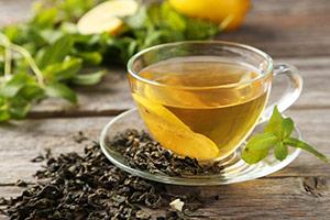 een kopje groene thee omringt door verse groene theebladeren