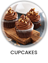 Een keukenblad met daarop een houte dienblad en daarop bruin met bruin/wit versierde cupcakes