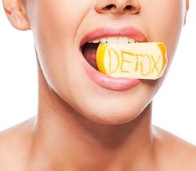 Mond van een vrouw met daarin een geel stuk zeep waar detox in staat gekrast