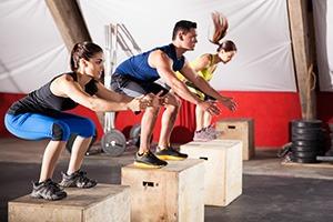 Drie mensen in sportkleding die op een houte kist springen/ staan in een squat positie