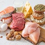 Tafel met daarop allerlei etenswaren zoals kaas, rauw vlees, rauwe kipfilet, rauwe zalm, nootjes, kruiden en eieren