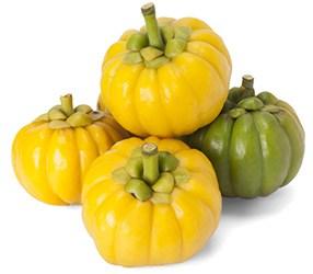 Vier gestapelde garcinia cambogia vruchten waarvan 3 geel en 1 groen