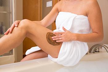 Vrouw in witte handdoek die gebruik maakt van de body scrub op haar been