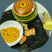 Stukjes gesneden gember naast een schaatje met oranje kurkuma poeder
