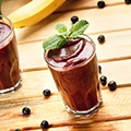 Een tafel met daarop 2 glazen met acai bessen smoothie en wat losse bessen op de tafel