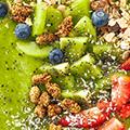 Groen pap met daarin kiwi, aardbeien, granen en blauwe bessen