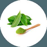 Een kleine houte lepel met groene thee poeder en een paar groene blaadjes