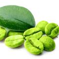 Een aantal losse groene koffie bonen op een witte achtergrond met een los groen blad van de koffie plant