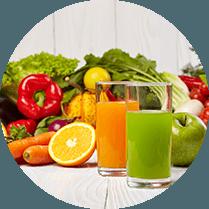 Tafel vol met groente en fruit en een glas groene sap en een glas oranje sap