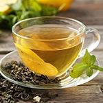 Een transparant kopje met groene thee en wat gedroogde groene thee op het schoteltje eronder