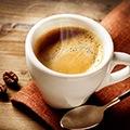 Een erg heet kopje koffie met daarnaast een kleine lepel
