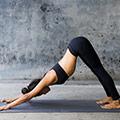 Een vrouw op een yoga-mat die op haar handen en voeten staat met haar kont naar boven geduwd