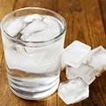Een tafel met daarop een glas ijskoud water en daarnaast een paar ijsklontjes