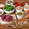 Een tafel vol met voeding waar ijzer in zit zoals vlees, tomaat en eieren