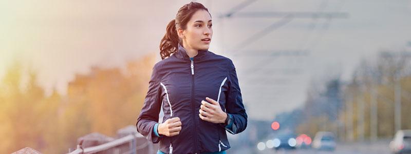 Vrouw die op een brug aan het joggen is en om haar heen kijkt
