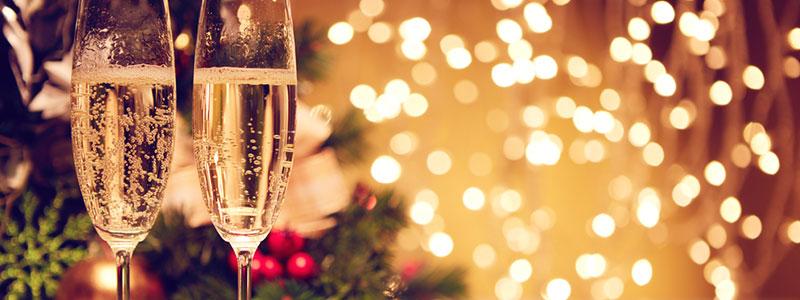 Een tafel met daarop 2 glazen champange en op de achtergrond kerstversiering en kerstlichtjes