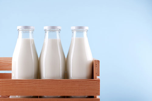Een houte kistje met daarin drie gesloten flessen melk