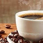 Houte tafel met daarop een wit kopje met koffie en daarnaast wat koffiebonen