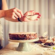 Een tafel met een chocolade taart die word versierd met kokosnoot suiker