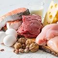 Tafel met voeding vol koolhydraten zoals kaas, vlees, kip, zalm, eieren en noten