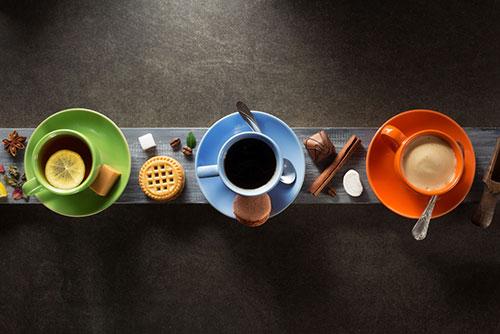 Groene kopje met thee, blauw kopje met koffie en oranje kopje met koffie
