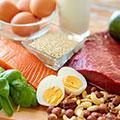 Een tafel met daarop gekookte eieren, zalm, nootjes, vlees, havermout en een glas met melk