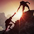 Een man bovenaan een berg die zijn hand uitreikt naar aan man die de berg op probeert te komen