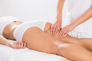 Vrouw die op een massagetafel ligt in haar witte ondergoed en wordt gemasseerd door iemand anders