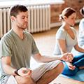 Een man en vrouw die aan het mediteren zijn tijdens een yoga-les