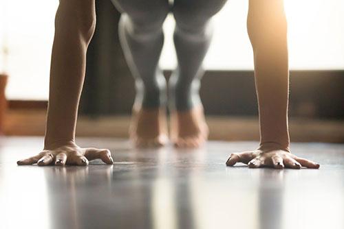 De armen en benen van iemand in sportkleding die aan het opdrukken is