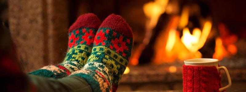 Een tafel met daarop de voeten van iemand die kerstmis sokken aanheeft en op de achtergrond een open haard