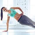 Een vrouw in sportkleding die een zijwaardse plank uitvoert met een hand op haar heup
