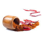 Een neergelegd potje met eruit rood peper poeder, een rode peper en wat schillen van rode pepers