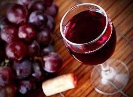 Een houte tafel met daarop een glas rode wijn en daarnaast een tros rode druiven
