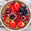 Roze schaaltje met daarin roze yoghurt versierd met fruit zoals aardbeien, blauwe bessen en granen