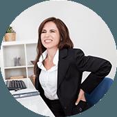 Vrouw in zwart pak die op een blauwe bureaustoel zit en haar handen in haar rug heeft door last van rugpijn