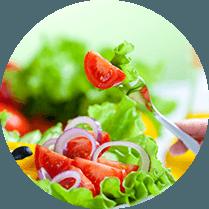 Een salada met sla, tomaat, rode uien en paprika en een vork met daarop wat sla en een stuk tomaat