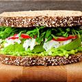 Zijkant van een sandwich met bruin brood en groente ertussen