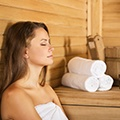Een vrouw in een handdoek die aan het genieten is in een sauna